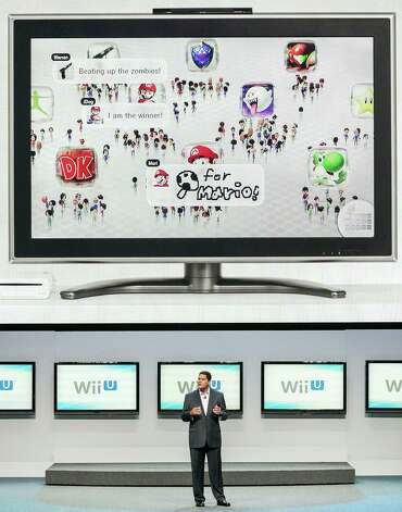 "FILE - In this June 5, 2012 file photo, Reggie Fils-Aime, president and CEO of Nintendo America, Inc., presents the Wii U as the next-generation game console at the Nintendo All-Access presentation at E3 2012 in Los Angeles. It can scan zombies, replace a TV remote, open a window into virtual worlds and shoot ninja stars across a living room. It's the Wii U GamePad, the 10-by-5-inch touchscreen controller for the successor to the Wii out Sunday, Nov. 18, 2012, and if you ask the brains behind the ""Super Mario Bros."" about it, they say it's going to change the way video games are made and played. (AP Photo/Damian Dovarganes, File) Photo: Damian Dovarganes"