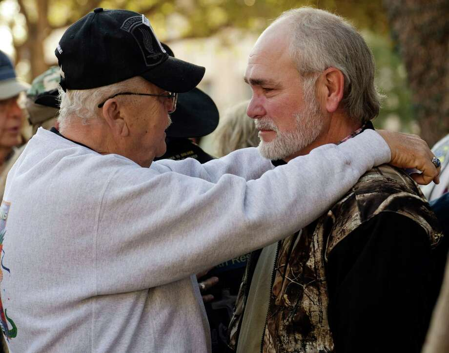 Johnie Lee Qualls, left, comforts and talks with Terry Johnson, Friday, Nov. 16, 2012, in Midland, Texas, before a community prayer service to pray for all those involved in an incident Thursday, where four veterans were killed and 16 other people were injured when a train slammed into a parade float carrying the returning heroes to a banquet. (AP Photo/Reporter-Telegram, Tim Fischer) Photo: Tim Fischer, Associated Press / Reporter-Telegram