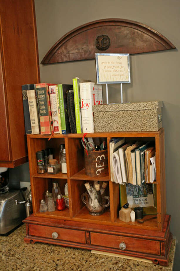 Spices, recipe books and utensils stored next to the stove.
