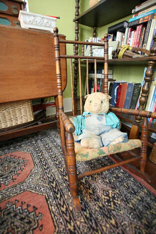A vintage stuffed animal sits in a rocker in Janyce Sisson's bedroom.