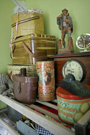 An assortment of vintage items on shelves in the guest bedroom; baskets serve as storage.