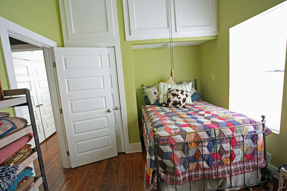 A colorful diamond-patterned quilt covers the bed in the guest bedroom. Janyce Sisson had a new longleaf pine floor installed in the bedroom after using the original wood to repair the damaged floor in other parts of the house.