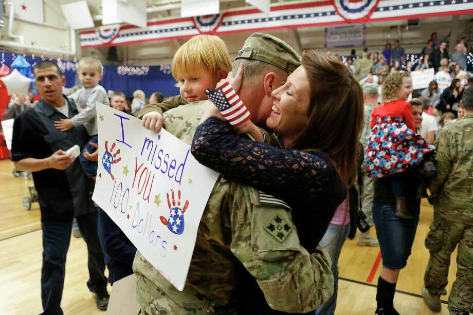 Who:Master Sgt. Adam Shaw and his wife, Mona, and son, Gavin. Where: Fort Carson, Colo. When: Nov. 4, 2012. Details: Shaw was back from a nine-month deployment. Photo: Marc Piscotty, Getty Images / 2012 Getty Images