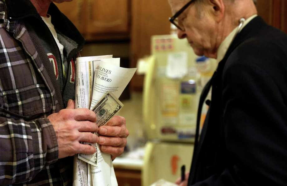 In this Tuesday, Oct. 30, 2012 photo, patient Joe Logsdon holds $5 in his hand to pay for his office visit as Dr. Russell Dohner, right, walks past in Rushville, Ill. When Dohner started practicing medicine in Rushville in 1955, he charged $2, the going rate around town for an office visit but has since raised it to $5. Photo: Jeff Roberson, AP / AP