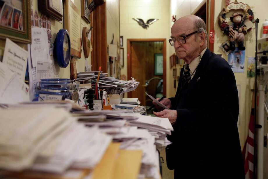 In this Tuesday, Oct. 30, 2012 photo, Dr. Russell Dohner looks over paper records between seeing patients in Rushville, Ill. His office has no fax machines, or computers, or other forms of modern technology. Medical records are kept on hand-written index cards, stuffed into row upon row of filing cabinets. Photo: Jeff Roberson, AP / AP