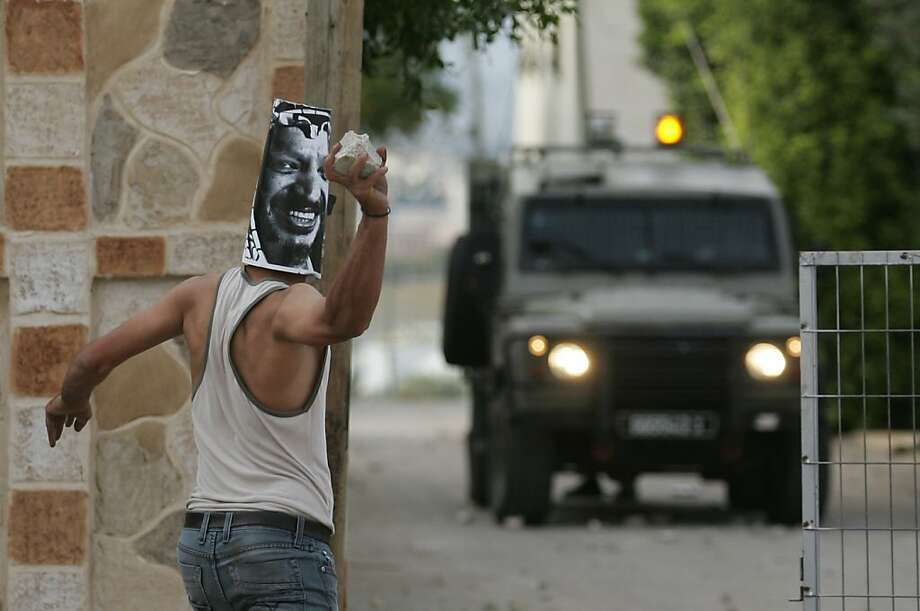 Those who throw stones: A Yasser Arafat fan hurls a rock at an Israeli military truck during clashes between Palestinians and Israeli security forces at the Jalama checkpoint in the West Bank near Jenin. Photo: Saif Dahlah, AFP/Getty Images