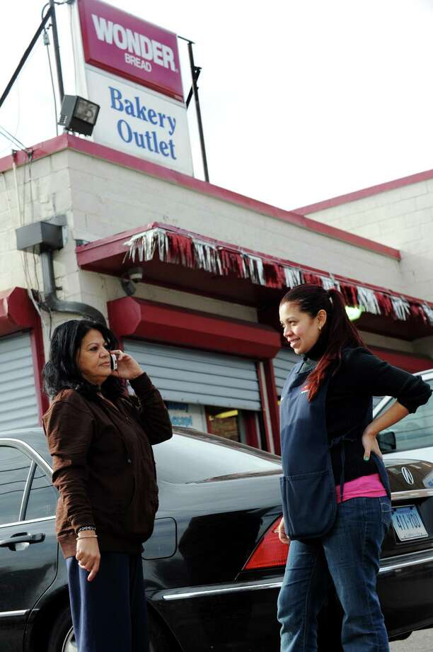 Wonder Bread Bakery Outlet clerks Marisol Sanchez and Cecia Villatoro talk outside the store on Wells Street in Bridgeport, Conn. on Friday, Nov. 16, 2012. Nearly 200 Connecticut workers face losing their jobs after Hostess Brands Inc. announced itâÄôs going out of business. Hostess employs about 200 workers in Connecticut in non-bakery retail and distribution facilities. Photo: Cathy Zuraw / Connecticut Post