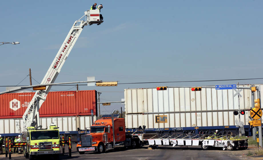 Workers use a Midland Fire Department ladder truck to photograph the scene of the crash, Friday Nov. 16, 2012, involving a Union Pacific train and a parade float carrying military veterans in Midland, Tx. Four veterans were killed in the accident which occurred Thursday afternoon. Photo: Edward A. Ornelas, San Antonio Express-News / © 2012 San Antonio Express-News