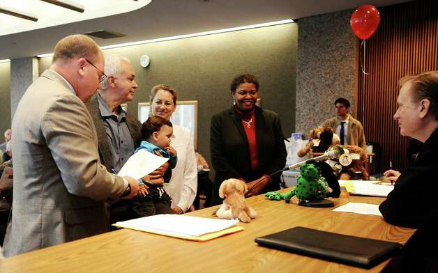 Friends and family of Beth and William Salazar join Judge Randy Shelton of the 279th District Court at the Jefferson County Courthouse Jury Impaneling Room to celebrate the consummation of adoption of Maxwell Salazar on November 16, 2012. Photo taken: Randy Edwards/The Enterprise