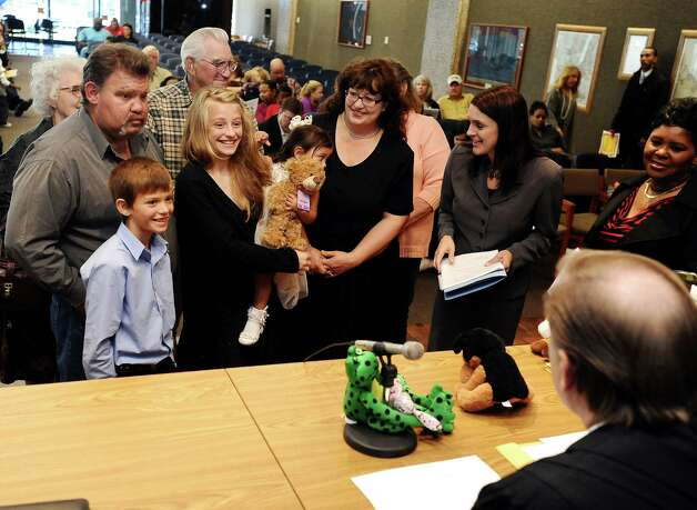 Friends and family of Diane and Ricky Gall, Sr. join Judge Randy Shelton of the 279th District Court at the Jefferson County Courthouse Jury Impaneling Room to celebrate the consummation of adoption of Isabella Gall on November 16, 2012. Photo taken: Randy Edwards/The Enterprise