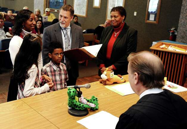 Nefertima Kelly joined Judge Randy Shelton of the 279th District Court at the Jefferson County Courthouse Jury Impaneling Room to celebrate the consummation of adoption of Xavier and Kierstin Kelly on November 16, 2012. Photo taken: Randy Edwards/The Enterprise