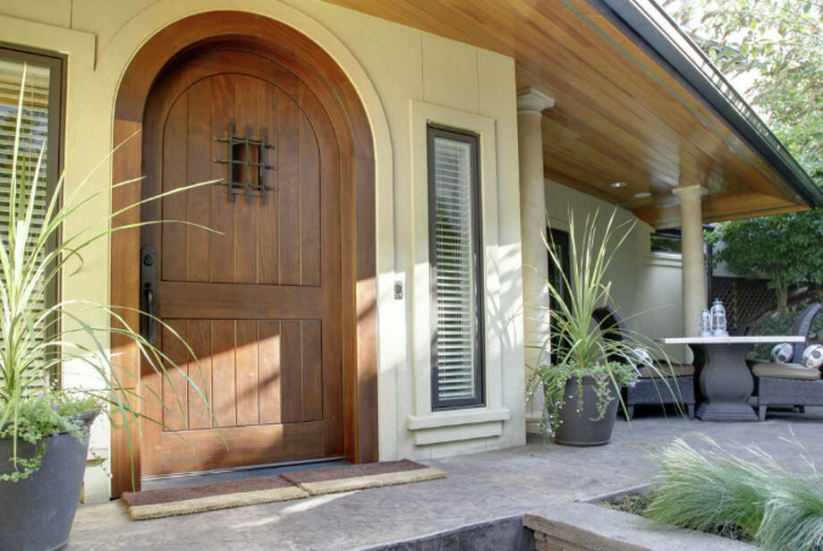 Front door of 4551 W. Raye St. The 6,300-square-foot house, built in 1953, has four bedrooms and 4.25 bathrooms -- including a master suite with a vaulted ceiling, exposed wood beams and a walk-in closet -- a den, a second kitchen, a wine cellar, an elevator, French doors, patios, decks, terraces, garages in the front and rear, and views of Puget Sound and the Olympic Mountains on a 10,297-square-foot lot. It's listed for $2.55 million. Photo: Steve Luke Hanson, Northwest Home Photography/Courtesy Mary Orvis, Orvis & Orvis