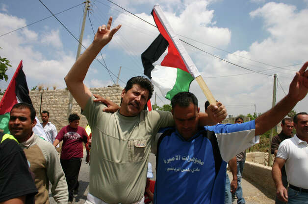 "Adeeb & Phil participate in a protest against the Israeli settlements in a still from the documentary ""5 Broken Cameras."" (Credit: Kino Lorber Inc)"