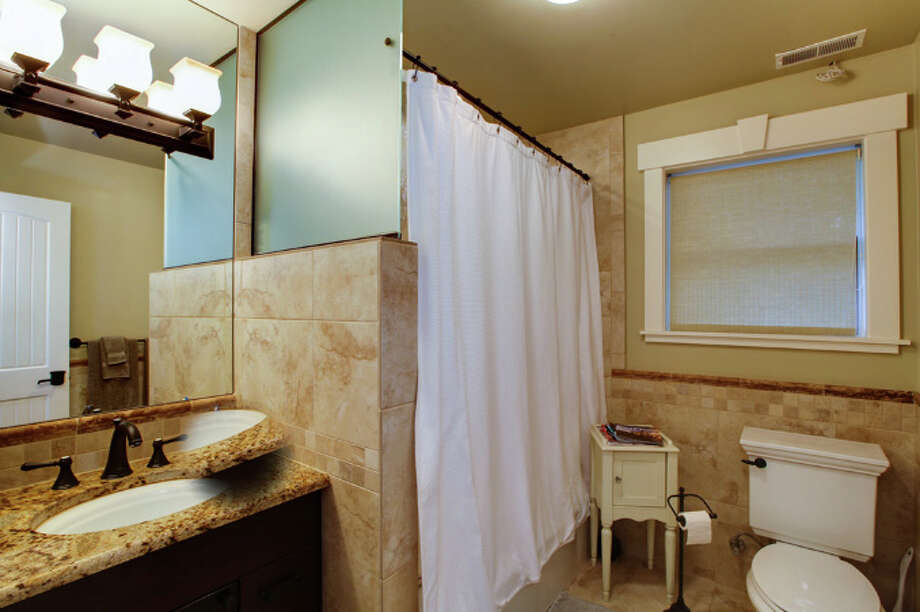 Bathroom of 4551 W. Raye St. The 6,300-square-foot house, built in 1953, has four bedrooms and 4.25 bathrooms -- including a master suite with a vaulted ceiling, exposed wood beams and a walk-in closet -- a den, a second kitchen, a wine cellar, an elevator, French doors, patios, decks, terraces, garages in the front and rear, and views of Puget Sound and the Olympic Mountains on a 10,297-square-foot lot. It's listed for $2.55 million. Photo: Steve Luke Hanson, Northwest Home Photography/Courtesy Mary Orvis, Orvis & Orvis