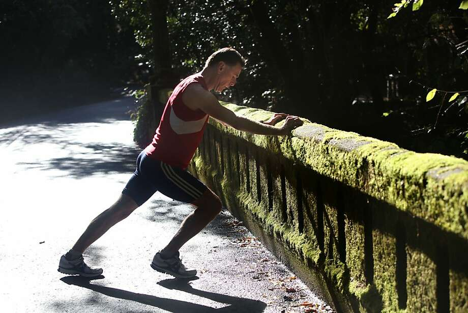 Mike Fanelli stretches after a run in Ross. He's cut back to an average of 50 miles a week, from 100 when he was younger. Photo: Liz Hafalia, The Chronicle