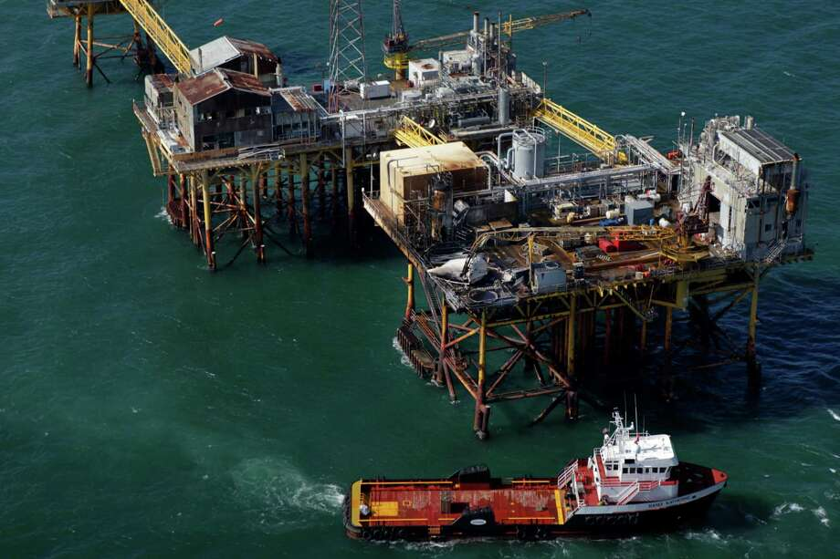 In this aerial photograph, a supply vessel moves near an oil rig damaged by an explosion and fire, Friday, Nov. 16, 2012, in the Gulf of Mexico about 25 miles southeast of Grand Isle, La. Four people were transported to a hospital with critical burns and two were missing. Photo: Gerald Herbert, Associated Press / AP