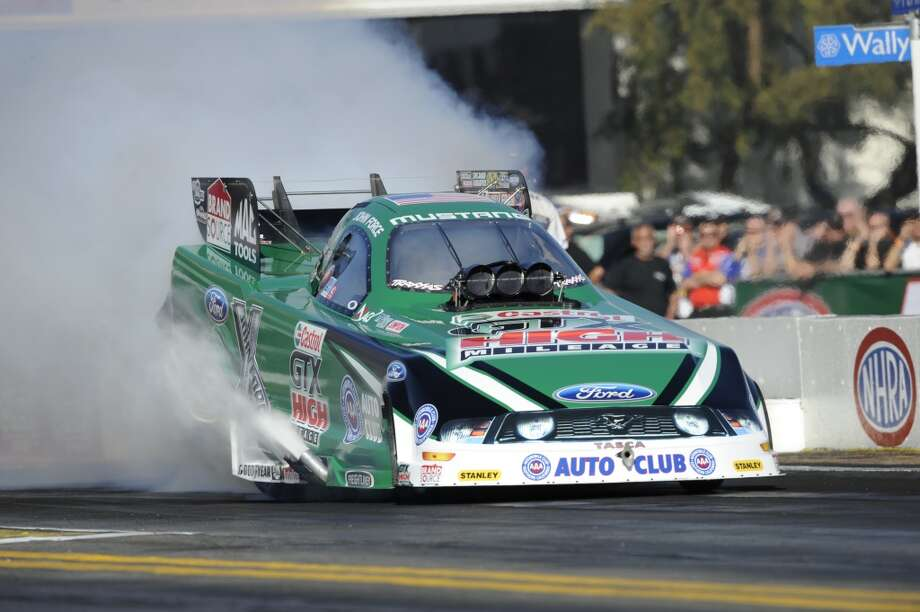 Fifteen NHRA Nitro Funny Car champion John Force does a burnout in his Castrol GTX NHRA Nitro Funny Car at the Texas Motorplex in Ennis, Texas. (NHRA photo)