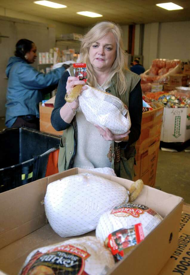 Kate Lombardo, executive director of the Food Bank of Lower Fairfield County in Stamford, Conn., holds one the turkeys donated by the Stamford Police Association on Friday November 16, 2012. Lombardo says that the Food Bank has already distributed around 8000 turkeys and they need about 2000 more. Photo: Dru Nadler / Stamford Advocate Freelance