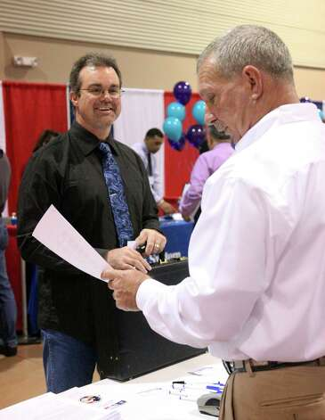 Job seeker Travis Martin (Left) talks to Jay Whitaker from Bassler Energy Services, Dilley Texas about employment at a job fair that the Tx Workforce Commission and Tx Veterans Commission is hosting at Expo Hall on the Freeman Coliseum grounds, 3201 E. Houston St. Thursday November 15, 2012 Photo: Juanito M Garza, San Antonio Express-News / San Antonio Express-News