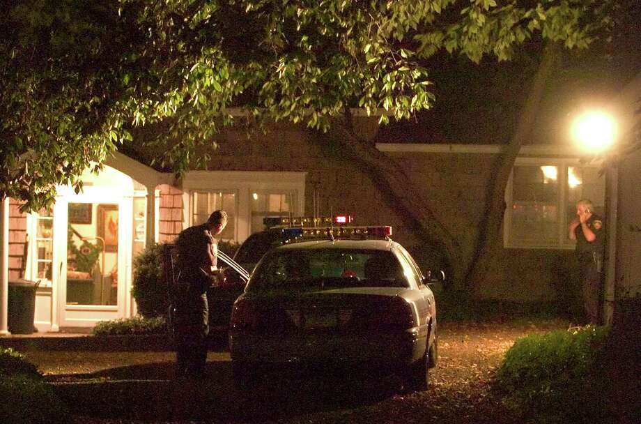 Stamford police officers investigate the homicide of Joanne Trautwein, who was found dead inside her home at 1260 Rock Rimmon Road. Photo: Chris Preovolos, Stamford Advocate / Stamford Advocate