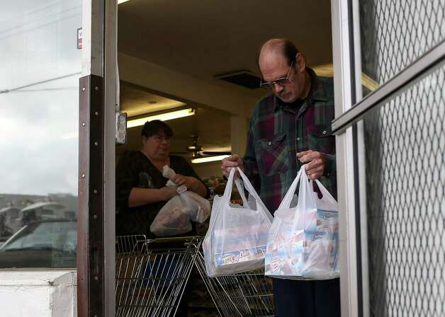 SAN LEANDRO, CA - NOVEMBER 16:  Customers carry bags of Hostess products as they leave a Wonder Hostess Bakery Outlet on November 16, 2012 in San Leandro, California. Hostess Brands, the maker of Twinkies, Ding Dongs and Wonder Bread, announced plans to liquidate its assets and lay off nearly 18,500 employees due to a workers strike brought on by an imposed contract that would cut workers' wages by 8 percent. Photo: Justin Sullivan, Getty Images / 2012 Getty Images