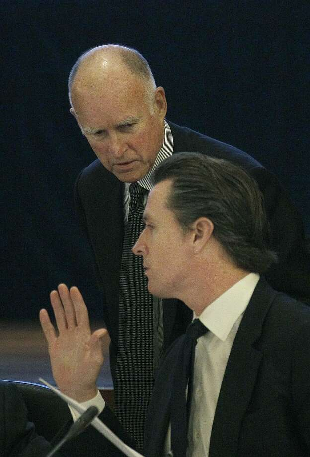 Gov. Jerry Brown, left, talks with Lt. Gov. Gavin Newsom at the UC Board of Regents meeting in San Francisco, Wednesday, Nov. 14, 2012. Brown is set to make his first appearance where he's expected to urge UC officials to control costs and avoid raising tuition. (AP Photo/Jeff Chiu) Photo: Jeff Chiu, Associated Press
