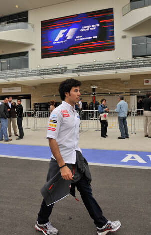 Mexican Sergio Perez walks along the Circuit of the America's pit lane Thursday. Practice for the United States Grand Prix begins Friday morning with the race scheduled for Sunday. Photo: Express-News