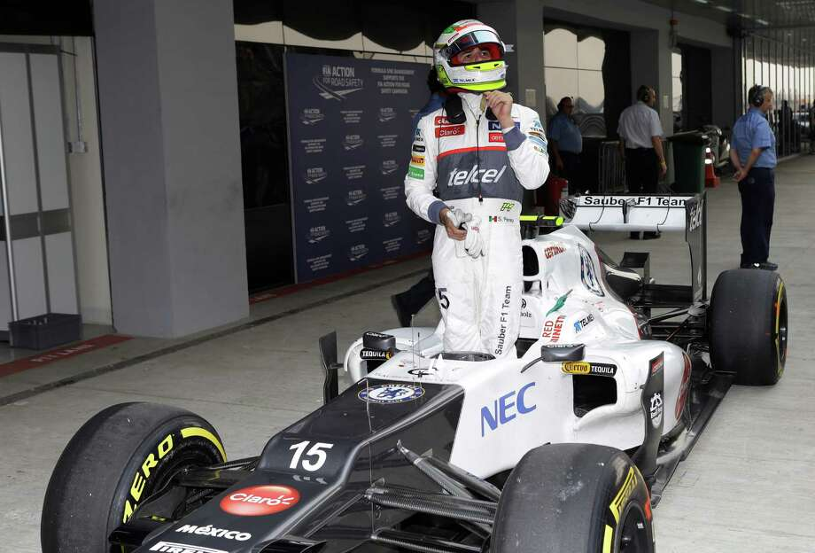 Sauber driver Sergio Perez of Mexico stands in his car after finishing eighth fastest in the qualifying session for the Indian Formula One Grand Prix at the Buddh International Circuit in Noida, on the outskirts of New Delhi, India, Saturday, Oct. 27, 2012. (AP Photo/Mark Baker) Photo: Mark Baker, Associated Press / AP