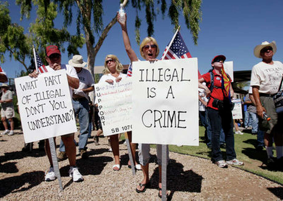 Judy Schulz, front, cheers as her husband Richard Schulz, left, both of Glendale, Ariz., as they joined hundreds supporting Arizona's new law on illegal immigration as they listen to speakers near the capitol Saturday, June 5, 2010, in Phoenix. (AP Photo/Ross D. Franklin) Photo: Ross D. Franklin, AP / AP