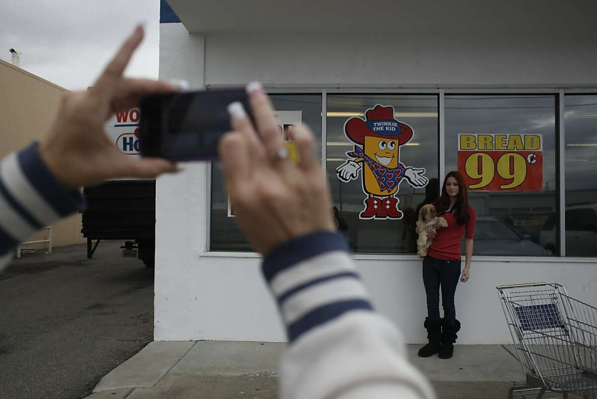 Lisa Kelly snaps a photo of her daughter, Kendall, outside the Wonder Hostess Bakery Thriftshop in San Leandro.