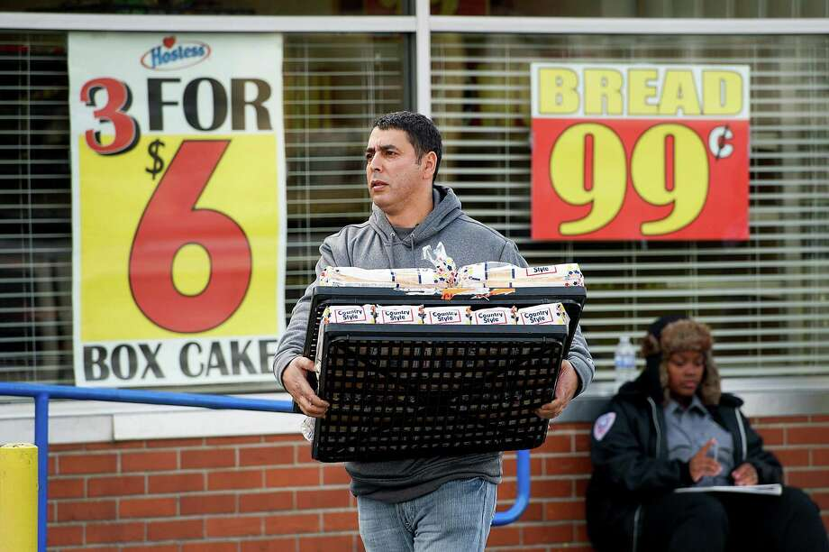 Kamal Moharam walks to his car carrying two racks of Hostess Brands Inc. Wonder Bread at the company's bakery outlet in Sacramento, California, U.S., on Friday, Nov. 16, 2012. Hostess, which also makes Wonder bread, Ding Dongs and Ho Hos, plans to fire more than 18,000 employees and liquidate assets after a nationwide strike by bakery workers crippled operations. Photographer: David Paul Morris/Bloomberg *** Local Caption *** Kamal Moharam Photo: David Paul Morris, Bloomberg / © 2012 Bloomberg Finance LP