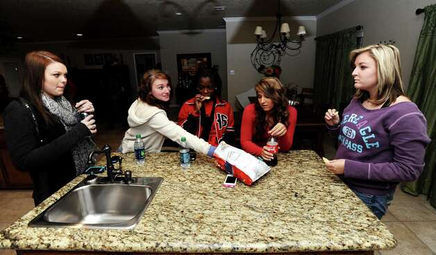 From left to right; Savannah Short, 14, Ashton Lawrence, 16, Kieara Moffett, 16, Macy Matthews, 15, and Rebekah Richardson, 17, chat at the Richardson household on Wednesday, November, 13, 2012.  The Kountze cheerleaders have grown significantly closer with everything they have worked through over the past two months. Photo taken: Randy Edwards/The Enterprise