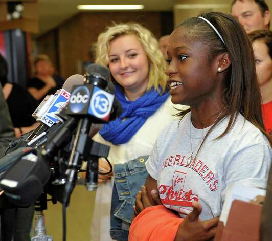 Cheerleader  Kieara Moffett, right, gives a statement to the media.  Attorneys were back in the 356 District Court Thursday morning before Judge Steve Thomas. After hearing more arguments before lunch, Thomas announced after lunch that he would grant the temporary injunction till the jury trial date of June 24, 2013.   The Kountze cheerleaders extended temporary restraining order was due to expire Thursday at midnight. Dave Ryan/The Enterprise Photo: Dave Ryan