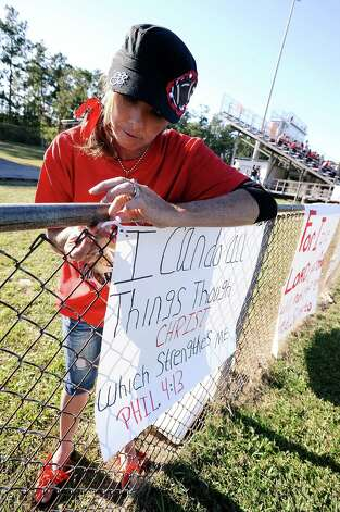 Crystal Bingham is the mother of two Kountze football players and is helping the cheerleaders secure their sings during the Kountze Middle School football game at Kountze High School on Thursday, September 20, 2012. Photo taken: Randy Edwards/The Enterprise Photo: Randy Edwards