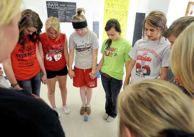 Kountze cheerleaders pray before practice on Wednesday. The girls Recently video chatted with Texas Governor Rick Perry who claims he supports the girl's religious expression. Photo taken Wednesday, October 17, 2012 Guiseppe Barranco/The Enterprise Photo: Guiseppe Barranco, STAFF PHOTOGRAPHER / The Beaumont Enterprise
