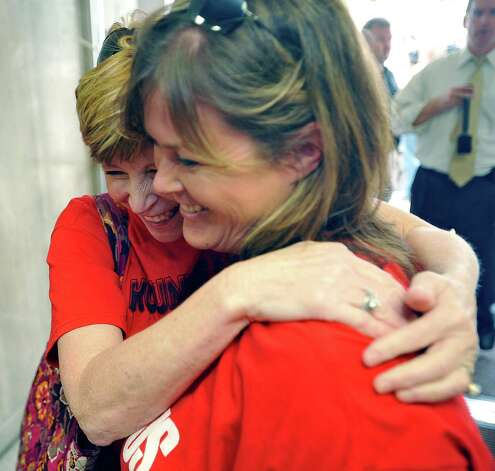 Susan Read, left, a high school student's mom, gets a hug from Ashley Brown, right, after she told her the judges decision. Attorneys were back in the 356 District Court Thursday morning before Judge Steve Thomas. After hearing more arguments before lunch, Thomas announced after lunch that he would grant the temporary injunction till the jury trial date of June 24, 2013.   The Kountze cheerleaders extended temporary restraining order was due to expire Thursday at midnight. Dave Ryan/The Enterprise Photo: Dave Ryan