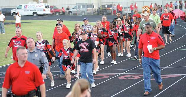 The cheerleaders enter the stadium escorted by their parents and officials. This was the first home football game in Kountze since the sign controversy started and since the Thursday hearing that determined the cheerleaders could or could not use their faith-based signs.  Dave Ryan/The Enterprise Photo: Dave Ryan