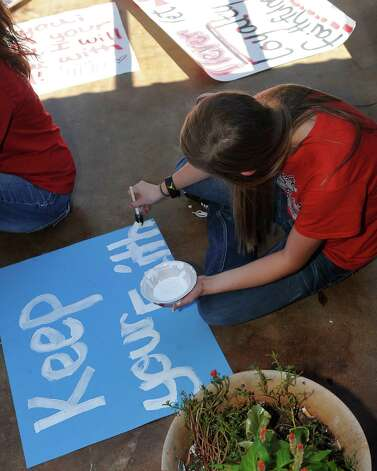 Kaylee Ledoux, a cheerleader, works on her own sign writing one  of her favorite sayings. Kountze cheerleaders, friends and supportive parents who are standing up for their kids and their beliefs, were making signs and painting car windows Wednesday afternoon that will be seen around Kountze in support of the cheerleaders who were told they could not put scripture on their football signs.  Each game this season, the Kountze cheerleaders have made Christian-themed run-through signs for the football players. The signs, which featured scripture verses, went viral and have now been stopped by the school district's leaders who were told by a group the signs were offensive and against the separation of church and state. Dave Ryan/The Enterprise Photo: Dave Ryan