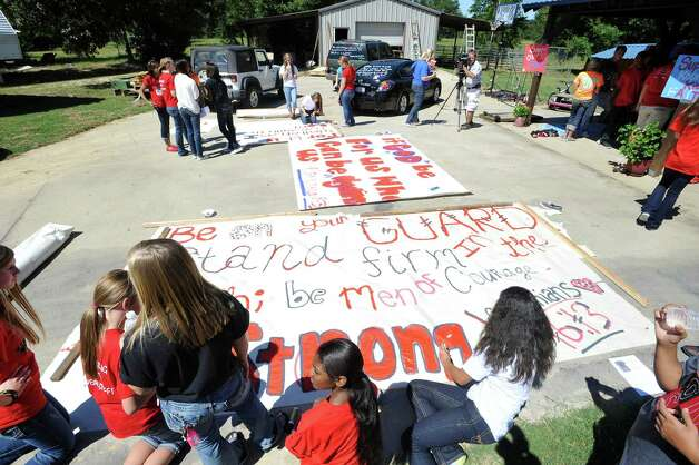 Kountze cheerleaders, friends and supportive parents who are standing up for their kids and their beliefs, were making large signs and painting car windows Wednesday afternoon that will be seen around Kountze in support of the cheerleaders who were told they could not put scripture on their football signs.  Each game this season, the Kountze cheerleaders have made Christian-themed run-through signs for the football players. The signs, which featured scripture verses, went viral and have now been stopped by the school district's leaders who were told by a group the signs were offensive and against the separation of church and state. Dave Ryan/The Enterprise Photo: Dave Ryan
