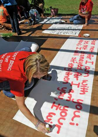 Brooke Coates, left, a cheerleader, paints a long sign on the patio. Kountze cheerleaders, friends and supportive parents who are standing up for their kids and their beliefs, were making signs and painting car windows Wednesday afternoon that will be seen around Kountze in support of the cheerleaders who were told they could not put scripture on their football signs.  Each game this season, the Kountze cheerleaders have made Christian-themed run-through signs for the football players. The signs, which featured scripture verses, went viral and have now been stopped by the school district's leaders who were told by a group the signs were offensive and against the separation of church and state. Dave Ryan/The Enterprise Photo: Dave Ryan