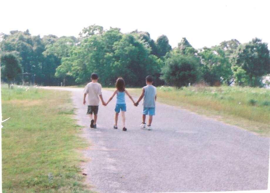 In 2001 Kristi and Nick Alvarado blended their families, including their four children. On a camping trip to Brenham that year, they took this photo of three of them, Ross, then 6, Kami, 4, and James, holding hands while walking down the road. Photo: Courtesy Photo