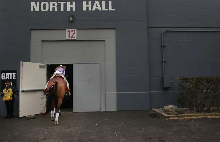 Maddie McClay, 16, with the drill team Flying Fillies, ducks as she enters the back door of Cow Palace for the start of The Grand National Drill Team Jackpot. Photo: Mike Kepka, The Chronicle