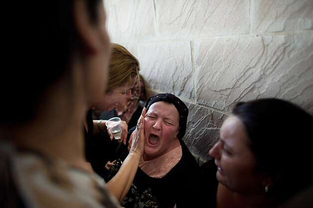 Relatives grieve at the funeral for Itzik Amsalem, 49, one of three people who was killed in a rocket attack Thursday in Kiryat Malachi, Israel. Photo: Uriel Sinai, Getty Images