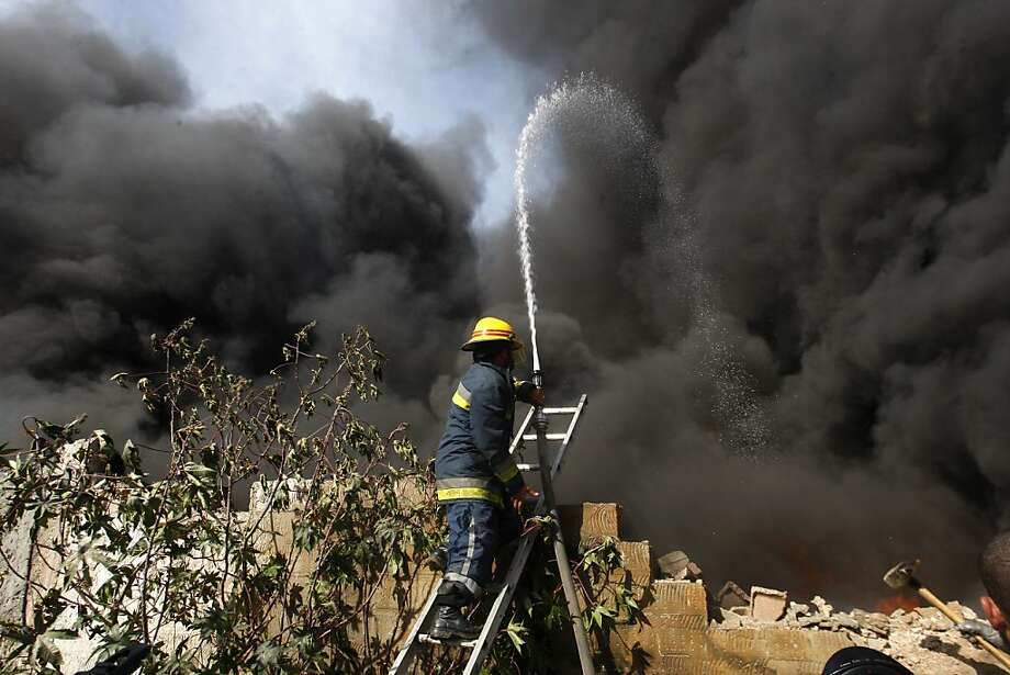 Palestinian firefighters try to extinguish a fire after an Israeli airstrike on a wood factory in east Jabaliya, northern Gaza Strip, Friday, Nov. 16, 2012. (AP Photo/Hatem Moussa) Photo: Hatem Moussa, Associated Press