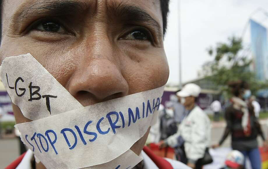 A Cambodian protester tapes his mouth shut in protest against discrimination of the Lesbian, Gay, Bisexual and Transgender (LGBT), in front of National Assembly, in Phnom Penh, Cambodia, Friday, Nov. 16, 2012. Nearly one thousand of protesters gathered on Friday to demand human rights and democracy in ASEAN bloc. (AP Photo/Heng Sinith) Photo: Heng Sinith, Associated Press