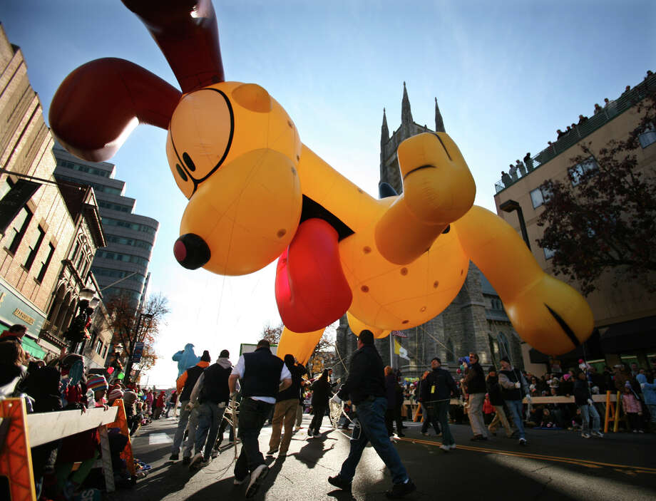 Volunteer balloon wranglers take Garfield's dog pal Odie for a spin to the entertainment of parade watchers. Photo: Brian A. Pounds, ST / Connecticut Post