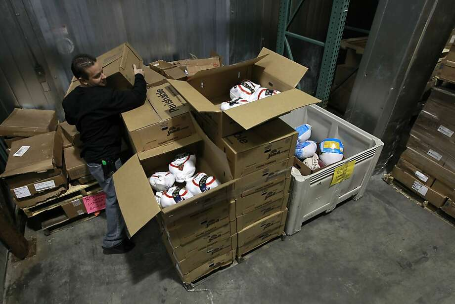 Joey Niehaus sorts through the available turkeys, which are in short supply at the San Francisco Food Bank. Photo: Michael Macor, The Chronicle