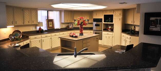 Clean countertops and the strong color of the decorations on the island draw a buyer's eye toward the kitchen. (Robin Jerstad/For the Express-Ne)