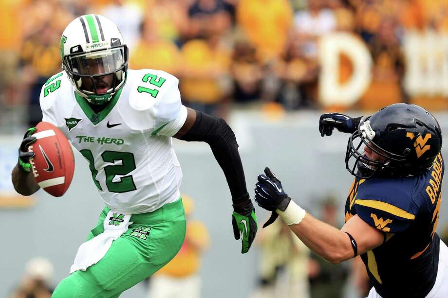 Marshall quarterback Rakeem Cato (12) avoids a sack by West Virginia's Jared Barber (33) during their NCAA college football game in Morgantown, W.Va., Saturday, Sept. 1, 2012. West Virginia won 69-34. (AP Photo/Christopher Jackson) Photo: Christopher Jackson, FRE / AP2012