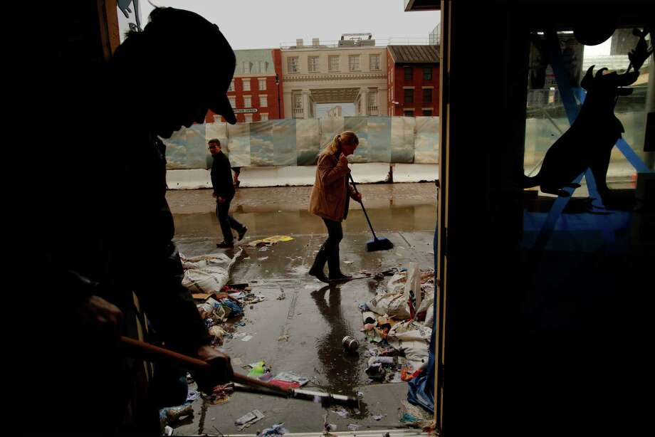 """Robert Zink, left, and Amanda Zink, center, start to clean up their store """"The Salty Paw,"""" which was completely flooded in the South Street Seaport area of lower Manhattan, New York. The tape on the windows was no match for the strength of Superstorm Sandy. Photo: Carolyn Cole, McClatchy-Tribune News Service / Los Angeles Times"""